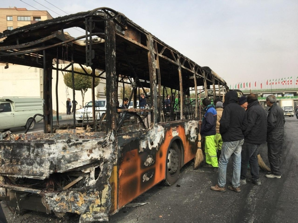 Iranians inspect the wreckage of a bus that was set ablaze by protesters during a demonstration against a rise in gasoline prices in the central city of Isfahan in this Nov. 17, 2019 file photo. — AFP