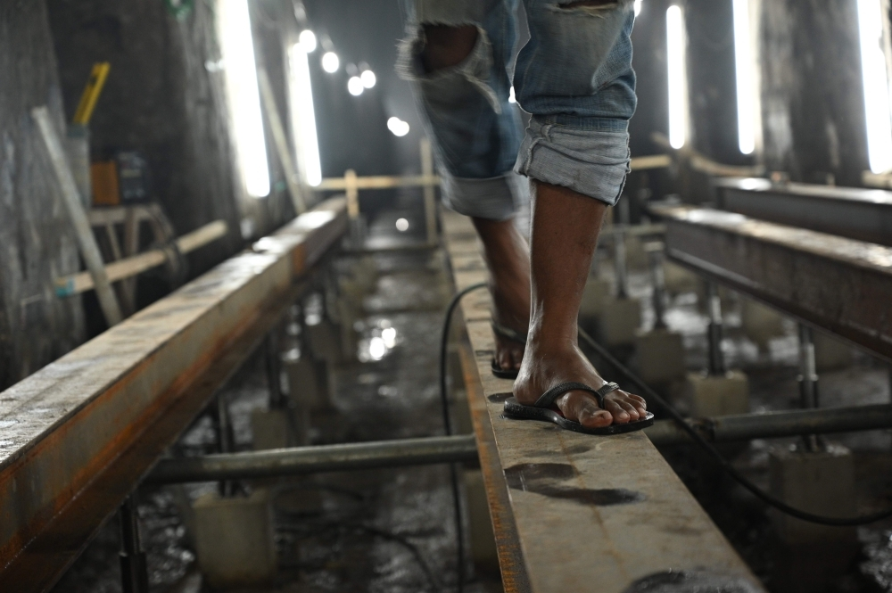 A worker walks along a metal pathway of the El Deposito, a Spanish-era water reservoir being rehabilitated for tourism, in San Juan town, suburban Manila, in this Nov. 6, 2019 file photo. — AFP.
