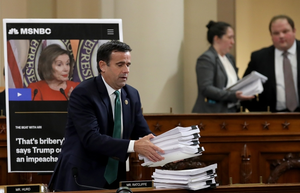 Rep. John Ratcliffe places a stack of transcripts of depositons on the dais as Lt. Col. Alexander Vindman, National Security Council Director for European Affairs, and Jennifer Williams, adviser to Vice President Mike Pence for European and Russian affairs testify before the House Intelligence Committee in the Longworth House Office Building on Capitol Hill in Washington on Tuesday. — AFP