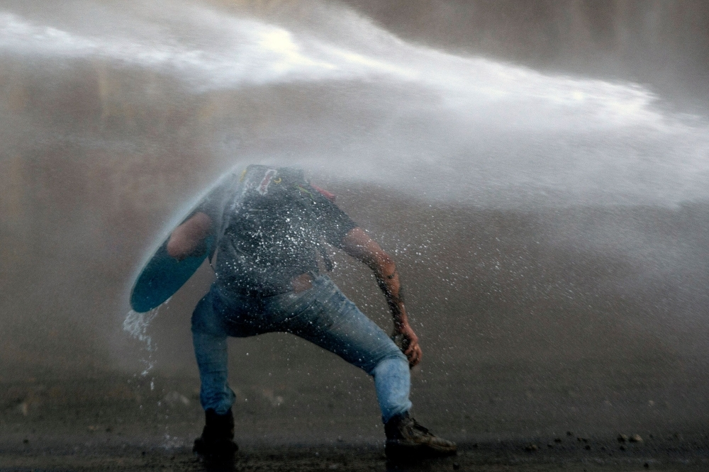 A demonstrator leans to elude the riot police water cannon during a protest against the government in Santiago on Tuesday. -AFP