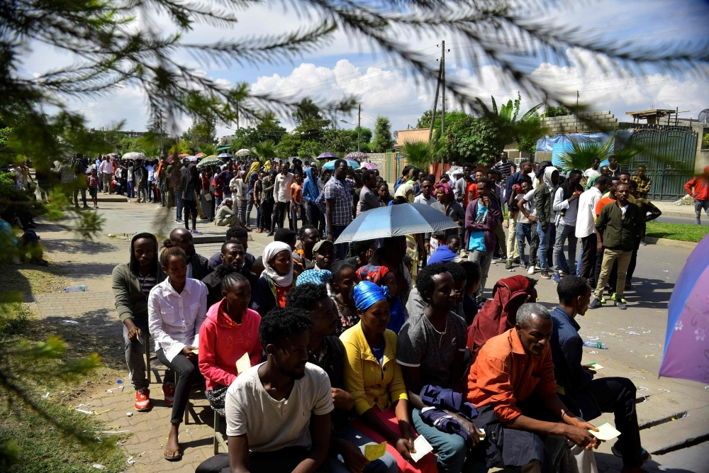 Voters pose for a picture with their identity documents while waiting in a queue to cast their vote during the Sidama referendum in Hawassa, Ethiopia, on Wednesday. — AFP