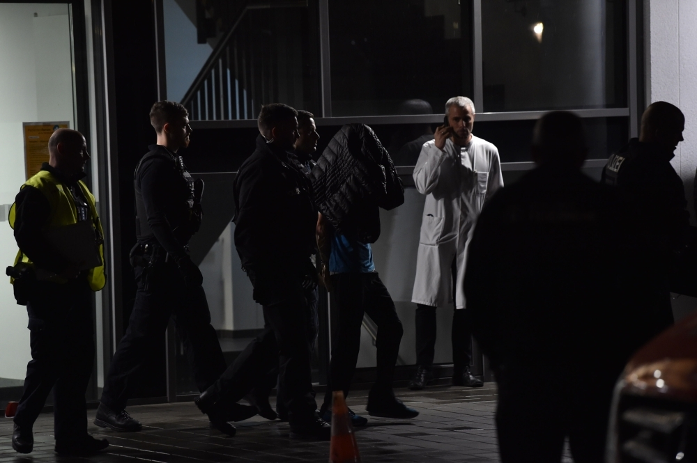 Policemen arrest a man after a doctor was stabbed to death as he delivered a lecture at the Schlosspark hospital in the western Berlin neighborhood of Charlottenburg, on Tuesday. — AFP