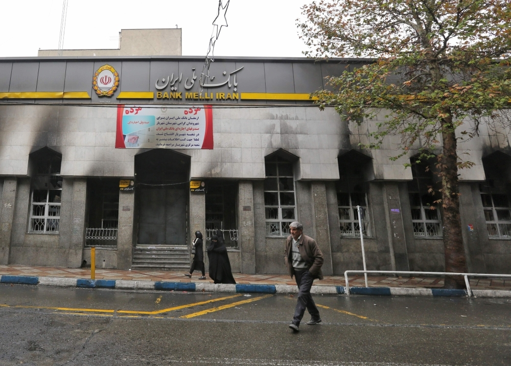 Iranians walk past the branch of a local bank that was damaged during demonstrations against petrol price hikes, in Shahriar, west of Tehran, on Wednesday. — AFP