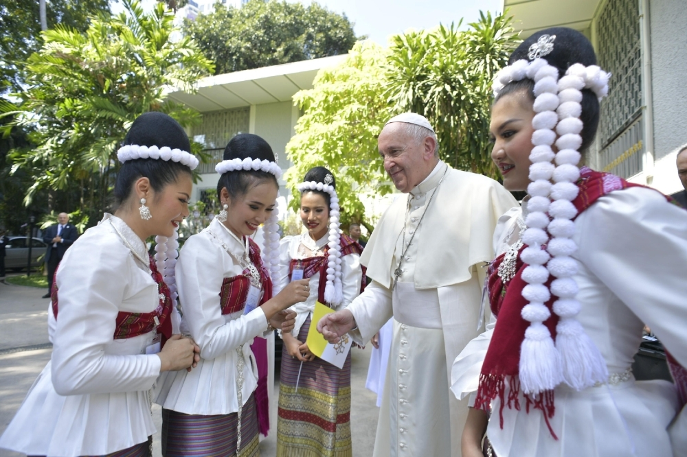 Pope Francis, second right, greets people during his arrival to the Apostolic Nunciature of the Holy See in Bangkok, Thailand, on Wednesday. — AFP