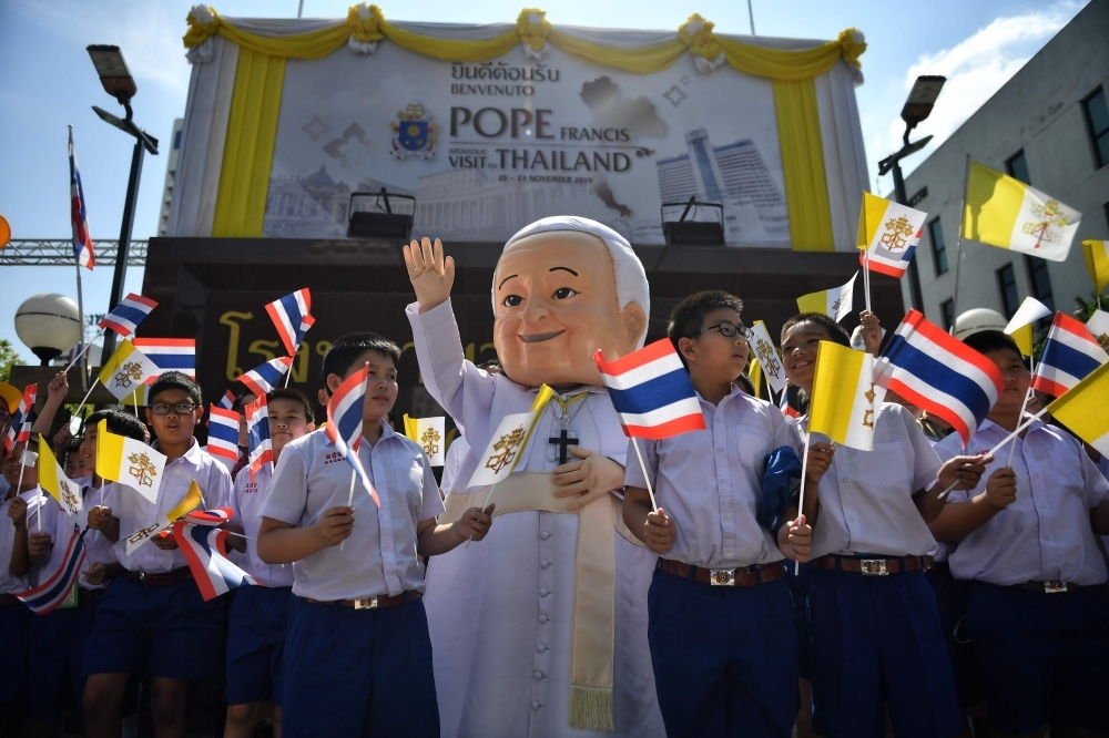 Catholic school children wait for Pope Francis' arrival outside of the Apostolic Nunciature of the Holy See in Bangkok, Thailand, on Wednesday. — AFP