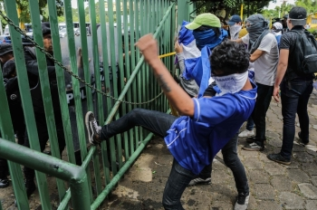 An anti-government protester kicks a riot police shield during a protest of students and relatives of political prisoners in front of a police line at the Universidad Centroamericana (UCA) in Managua on Tuesday. -AFP