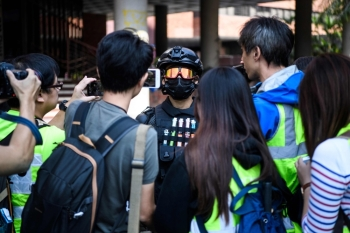 A male protester (C), who gave his age as 16, speaks to the media at the campus of the Hong Kong Polytechnic University in the Hung Hom district of Hong Kong on Wednesday. -AFP