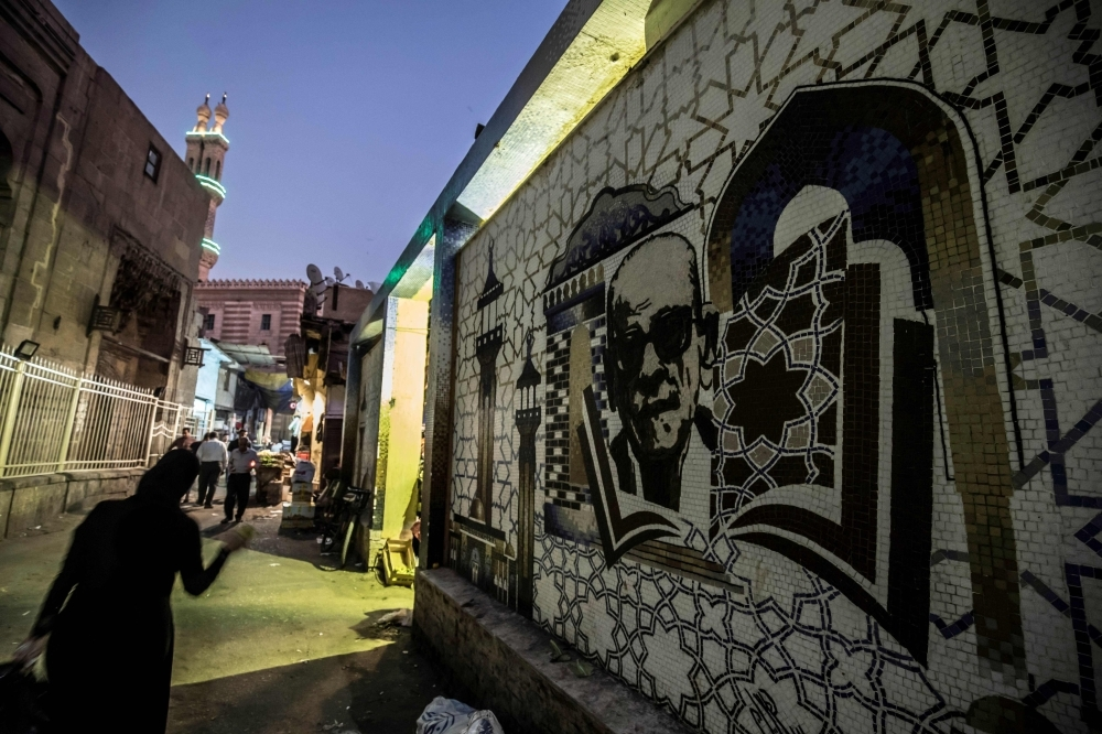 A mural depicting Egyptian novelist and Nobel prize winner Naguib Mahfouz is pictured behind the Al-Azhar mosque in downtown Cairo on Tuesday. — AFP