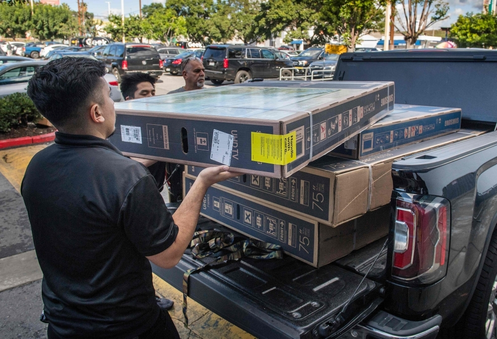Workers load four televisions onto a customer's vehicle during Black Friday sales in Los Angeles on Friday. -AFP