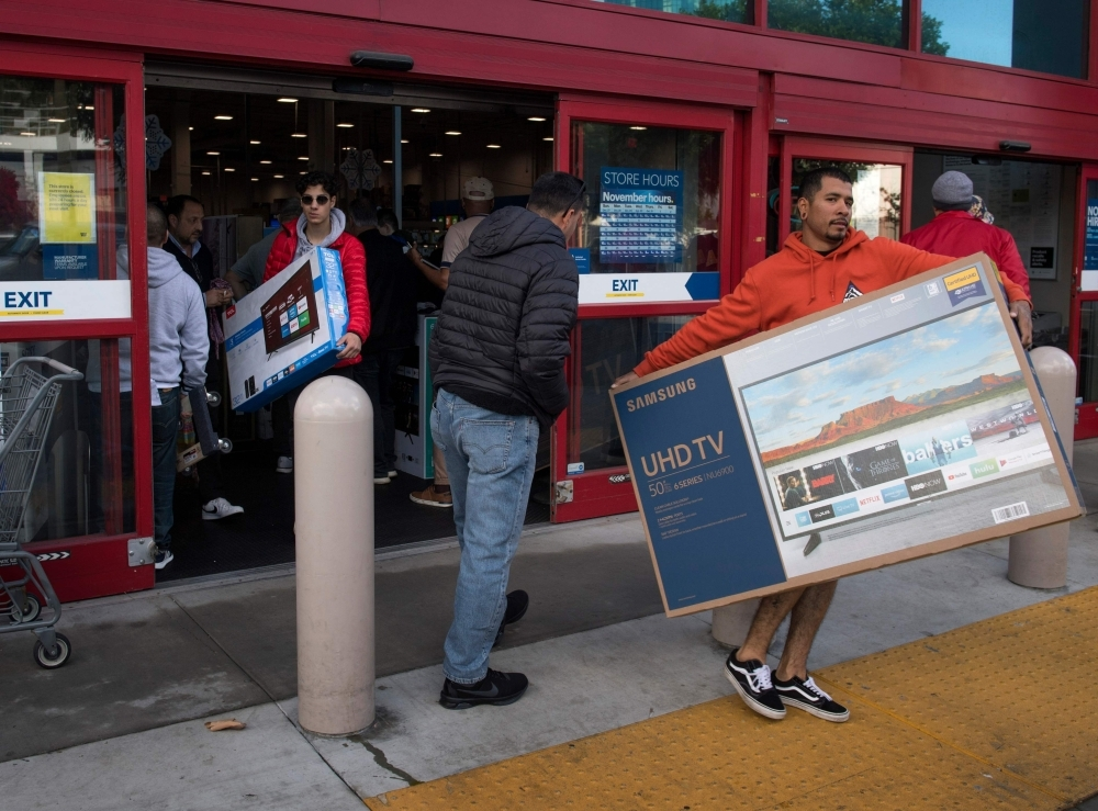 Shoppers carry televisions purchased from a store during Black Friday sales in Los Angeles on Friday. -AFP