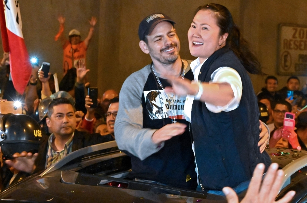 Peruvian politician Keiko Fujimori waves to supporters next to her husband Mark Villanella as she is released from prison in Lima on Friday.-AFP