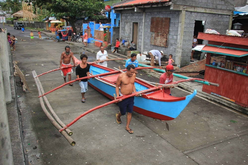 Residents carry to safety a wooden boat in Legaspi City, Albay province, south of Manila on Monday, as they prepare for Typhoon Kammuri. -AFP