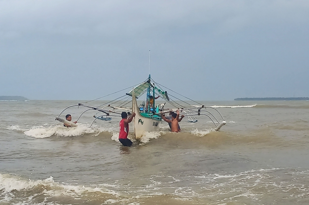 Residents help carry a wooden fishing boat into a secured area along the coast in Borongan town, Eastern Samar province, central Philippines, on Monday, as they prepare for Typhoon Kammuri.  — AFP