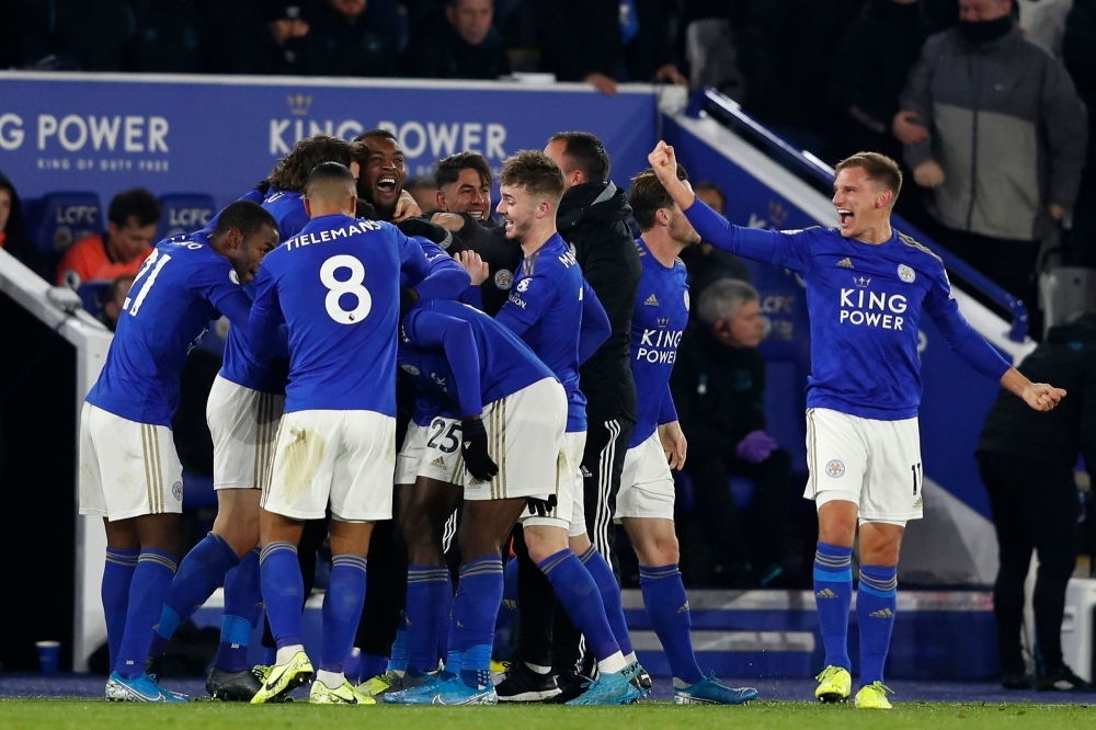 Leicester City's Nigerian striker Kelechi Iheanacho celebrates with teammates after scoring their late winning goal during the English Premier League football match between Leicester City and Everton at King Power Stadium in Leicester, central England, Monday. Leicester won the game 2-1. — AFP