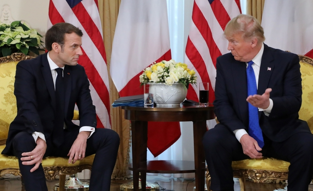 US President Donald Trump, right, France's President Emmanuel Macron react as they talk during their meeting at Winfield House, London, on Tuesday. — AFP
