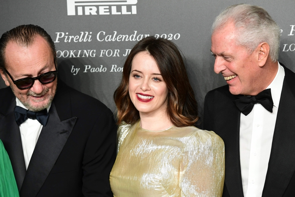 Italian photographer Paolo Roversi, left, and British actress Claire Foy, center, and Pirelli's CEO Marco Tronchetti Provera attend the presentation of the Pirelli 2020 Calendar