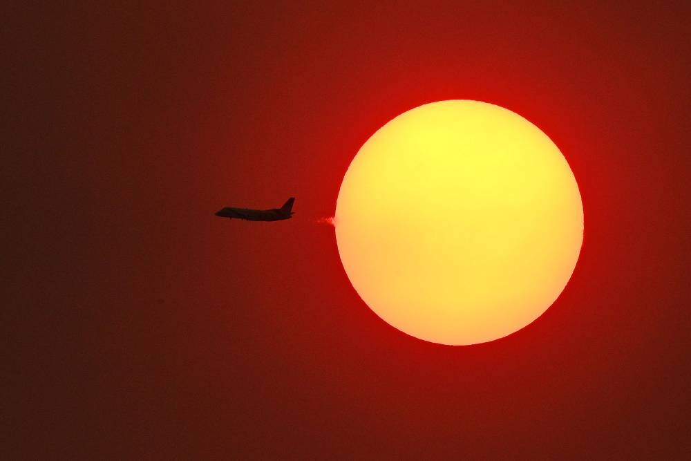 A passenger aircraft flying across the setting sun in Sydney, as smoke haze continues to hang over the city with more than 50 bushfires still burning across New South Wales. — AFP
