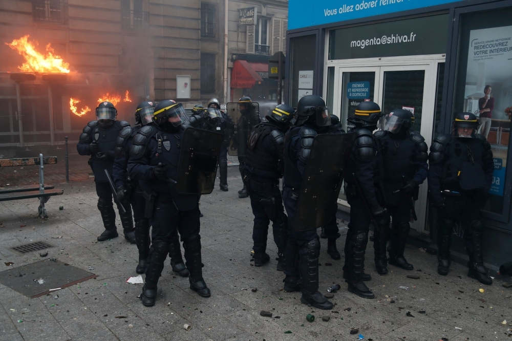 CRS riot police stand as fire is seen in the background during a rally against the pension overhauls, in Paris, on Thursday. — AFP