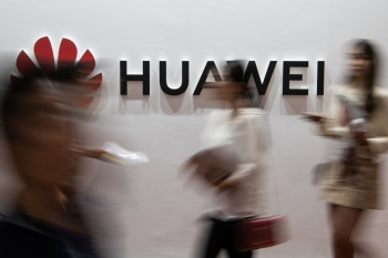 People walk past a Huawei logo during the Consumer Electronics Expo in Beijing in this Aug. 2, 2019 file photo. — AFP