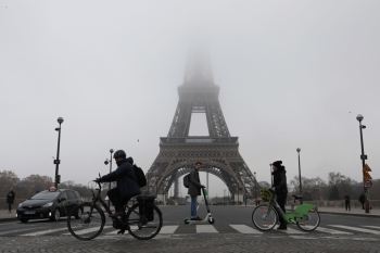 People ride bicycles and electric scooter past the Eiffel tower partially hidden by fog in Paris on Thursday. — AFP