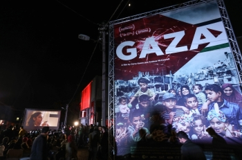 Palestinians watch a film during the opening ceremony of the Red Carpet Human Rights Film Festival in Gaza-Karama Palestine, in front of the abandoned Cinema Amer building in Gaza City, on Wednesday. — AFP