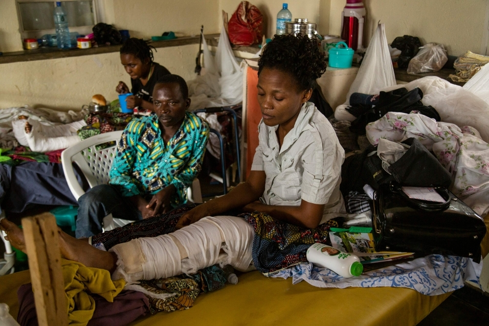 Kavugho Mbafumoja, right, 36, a survivor of an attack by an Armed Forces of the Democratic Republic of the Congo (FARDC) soldier, a few minutes after an attack that is attributed to the armed group of the Allied Democratic Forces (ADF), sits on a hospital bed the Beni General Hospital, in Beni, in this Dec. 3, 2019 file photo. — AFP
