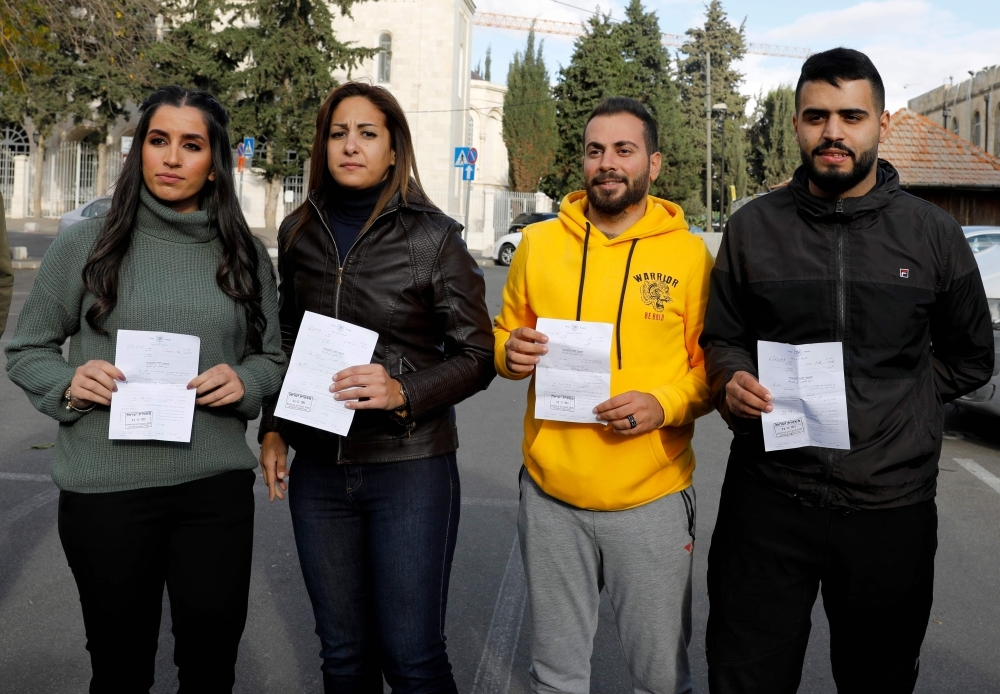 Palestinian journalists Dana Abou Shamsiyeh, left, Christine Renaoui second left, Ali Yassin, second right, and Amir Abed Rabbo, right, who were briefly detained by the Israeli authorities, is pictured upon their release in Jerusalem on Friday. — AFP