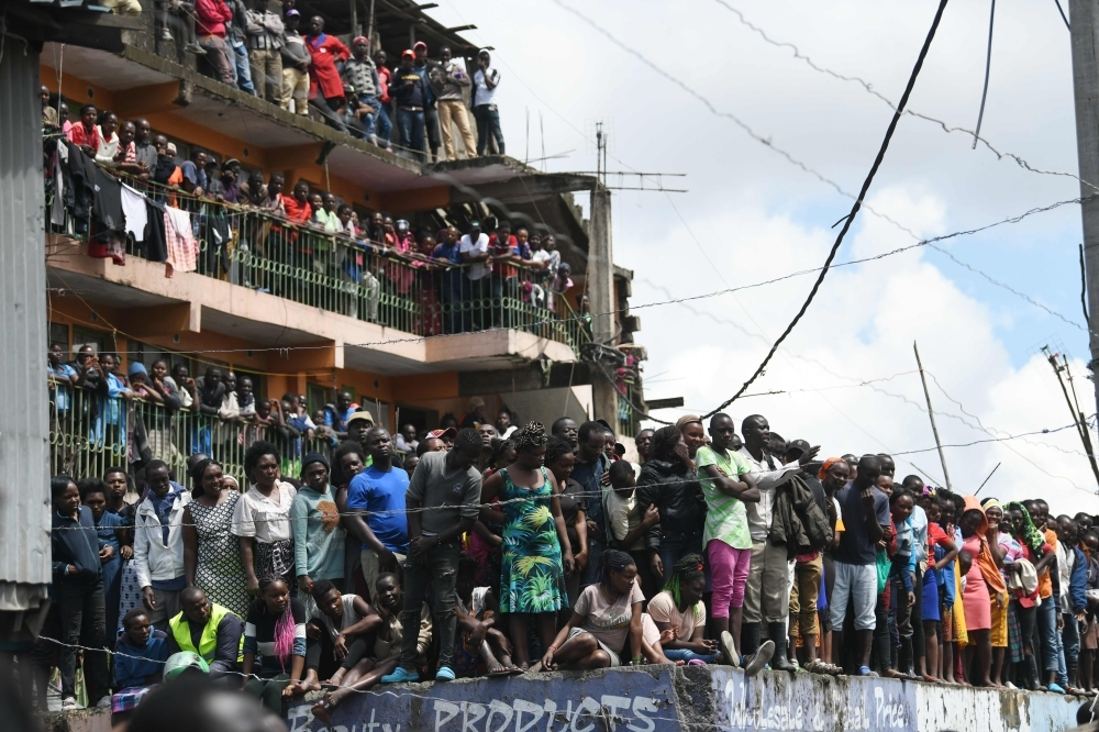 Curios onlookers stand around the scene of a collapsed six-story building in Nairobi, as search and rescue continue, on Friday. — AFP