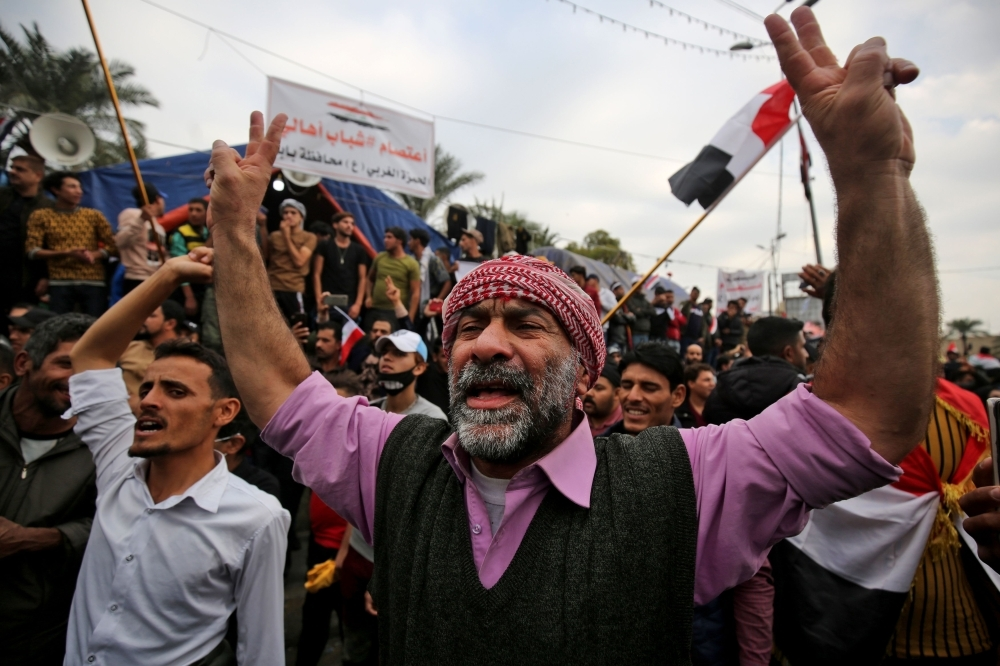 Iraqi demonstrators shout slogans as thee take part in an anti-government demonstration in the capital Baghdad's Tahrir Square on Friday. — AFP