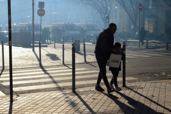 A man and his child walk to avoid tear gas smoke on the sidelines of a demonstration against the pension overhauls, in Bordeaux, France, on Thursday. — AFP