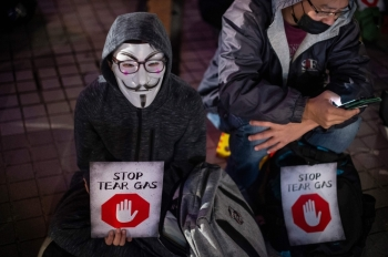 A participant wearing a Guy Fawkes mask holds a placard during a