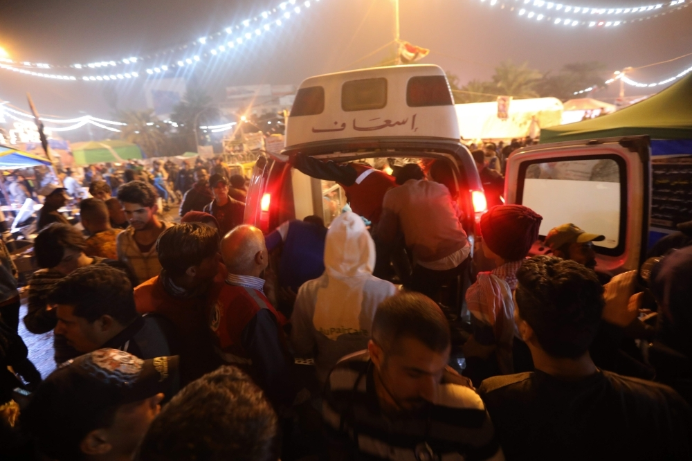An ambulance arrives in Tahrir square after unidentified men attacked an anti-government protest camp in Baghdad late on Friday. -AFP