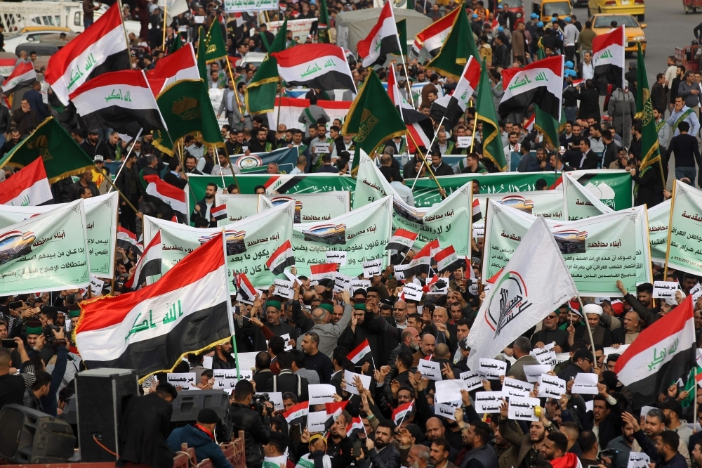 Iraqi demonstrators wave national flags and carry banners as the take part in an anti-government demonstration in the capital Baghdad's Tahrir Square, on Friday. -AFP