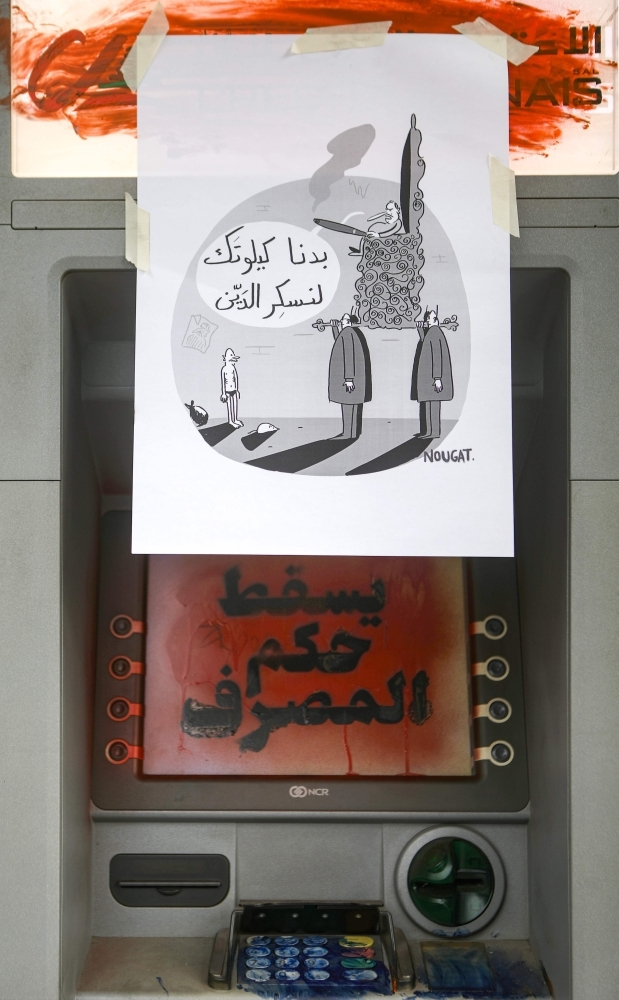 In this file photo taken on October 23, 2019, a sign is displayed on an ATM machine in the Lebanese capital Beirut showing a cartoon by local artist Mohamad Nohad Alameddine showing a skinny man stripped down to his underpants cowering in front of a leader carried in on a gilded throne, while a moustachioed politician, clutching a lit cigar, says in Arabic