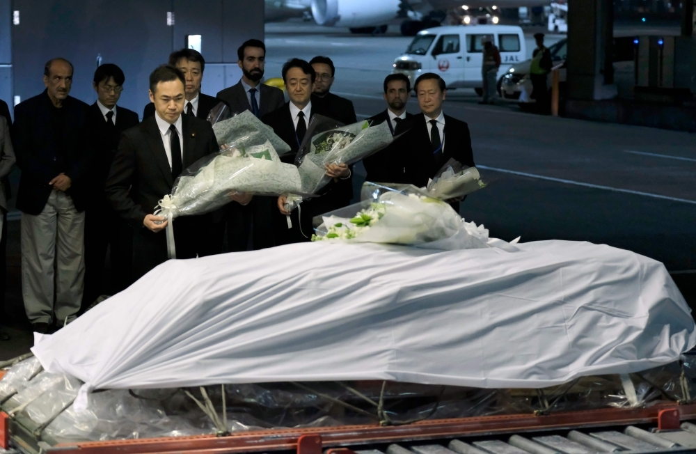 Keisuke Suzki (C), Japan's State Minister for Foreign Affairs, offers a bouquet over late Japanese physician Tetsu Nakamura's coffin upon arrival at Narita Airport in Chiba prefecture on Sunday. -AFP