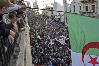 Algerians wave a national flag from a balcony as they watch anti-government demonstrators march in the capital Algiers on December 6, 2019, ahead of the presidential vote scheduled for December 12. -AFP