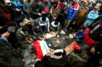 Iraqi protesters mourn and pray at the site where 17 people at least were killed and dozens more wounded overnight at Al-Khilani square in the capital Baghdad, amid ongoing anti-government demonstrations on Sunday. -AFP