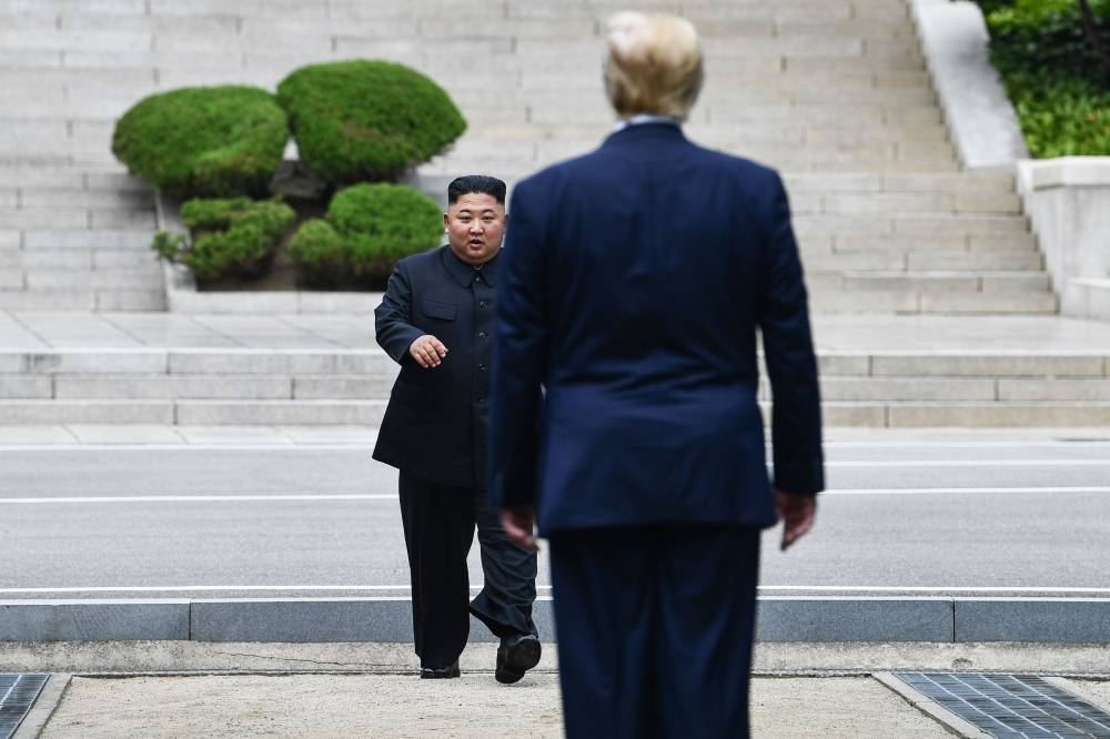 In this file photo taken on June 30, 2019 North Korea's leader Kim Jong Un walks to greet US President Donald Trump at the Military Demarcation Line that divides North and South Korea, in the Joint Security Area (JSA) of Panmunjom in the Demilitarized zone (DMZ).  -AFP