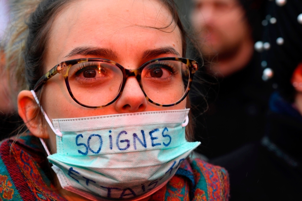 A woman wears a medical mask reading in French