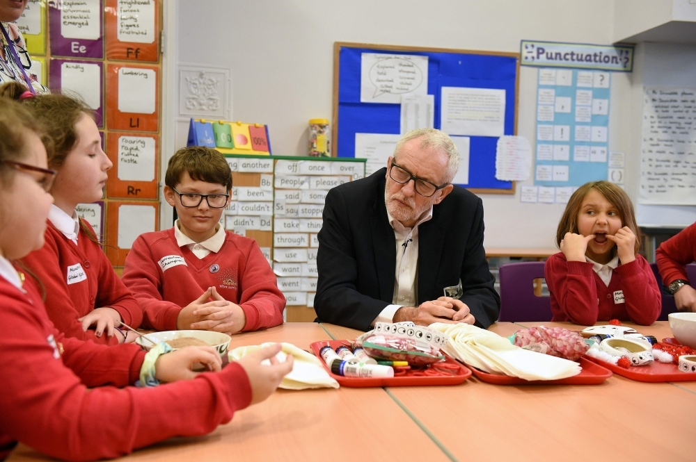 Opposition Labour party leader Jeremy Corbyn, second right, sits with schoolchildren during a campaign event at Sandylands Community Primary School in Morecambe, northwest England, on Tuesday. — AFP