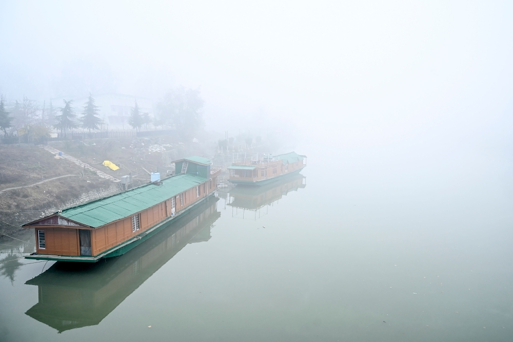 House boats are seen in Jhelum river amid fog in Srinagar on Tuesday. — AFP