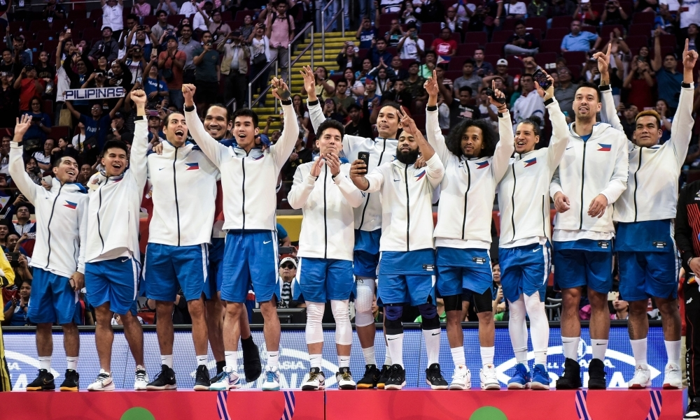 Players of the Philippines celebrate on the podium after winning gold medal in the men's final basketball event at the SEA Games (South East Asian Games) in Manila on Tuesday. — AFP