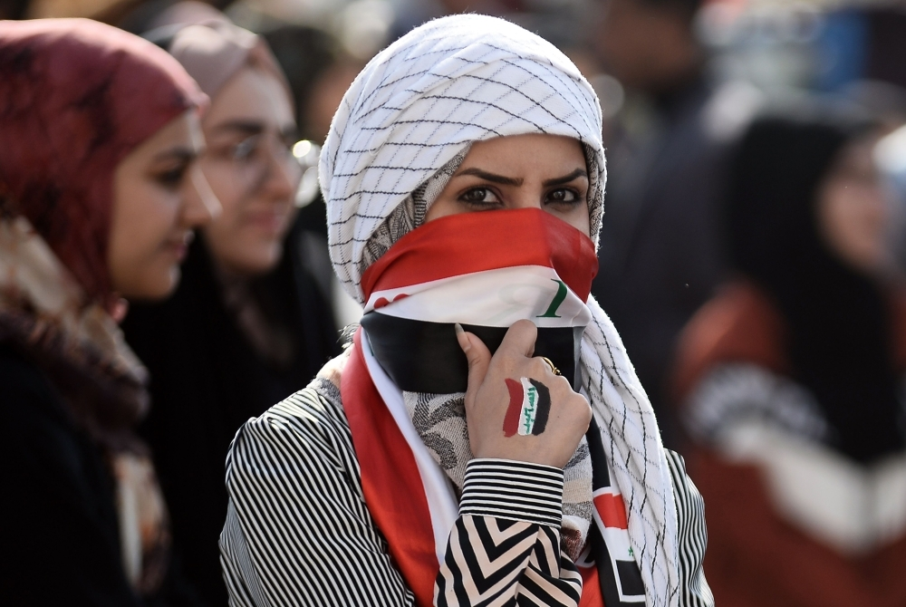 An Iraqi student covers her face with a national flag as she takes part in an anti-government demonstration in the central city of Najaf on Wednesday. — AFP