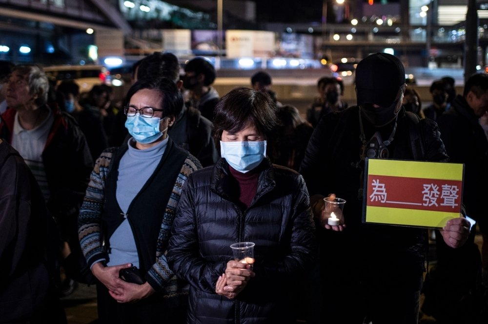 People hold electronic candles and placards during a Human Rights Day rally in Hong Kong on Tuesday. — AFP