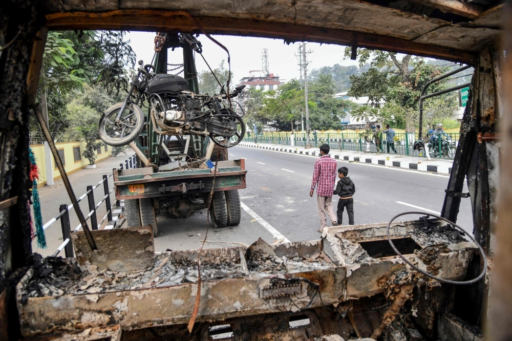 People walk past the wreckage of a vehicle which was set on fire by demonstrators during a protest against the government's Citizenship Amendment Bill (CAB) in Guwahati on Thursday. — AFP