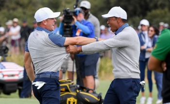 US players Justin Thomas (L) and Tiger Woods (R) celebrate winning the match during the second day of the Presidents Cup golf tournament in Melbourne on Friday. — AFP