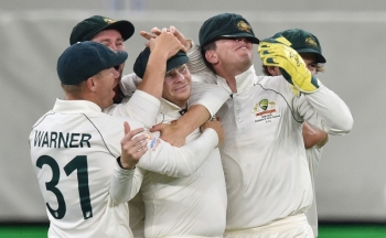 Australia's Steve Smith (3rd-L) is mobbed by his teammates after catching New Zealand captain Kane Williamson  on day two of the first Test cricket match between Australia and New Zealand at the Perth Stadium in Perth on Friday. — AFP
