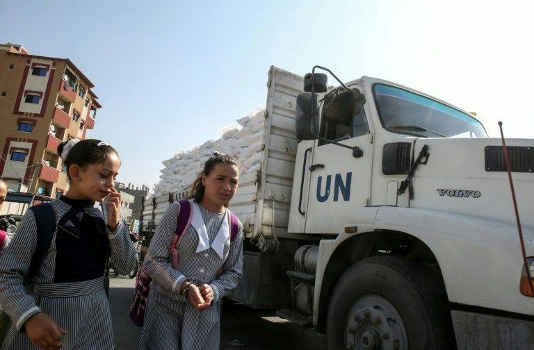 Palestinian schoolgirls walk past a United Nations aid truck transporting sacks of flour outside a UN compound in the southern Gaza Strip refugee camp of Rafah, on November 17, 2019 -AFP