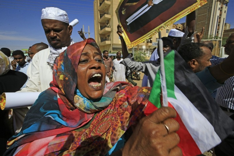 A supporter of deposed Sudanese president Omar Al-Bashir shouts and waves the national flag during a rally after his conviction of graft, outside a court in the capital Khartoum, on Saturday. -AFP