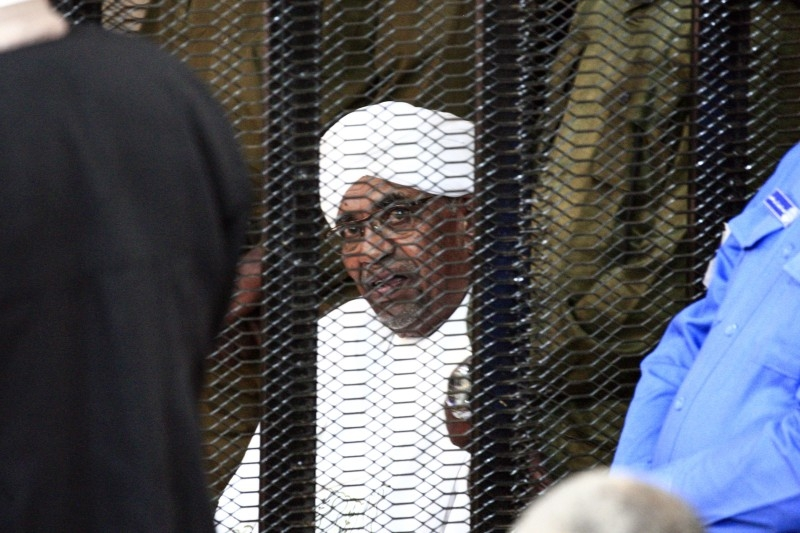 In this file photo taken on August 24, 2019 Sudan's deposed military ruler Omar Al-Bashir sits in a defendant's cage during his corruption trial in Khartoum. -AFP